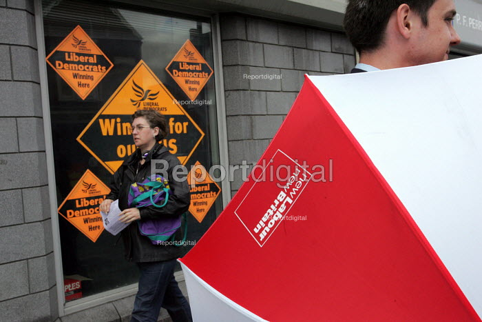 Labour Party campaigner with a new Labour umbrella outside the Liberal Democrat HQ on York Road, Hartlepool by election campaign - Mark Pinder - 2004-08-18
