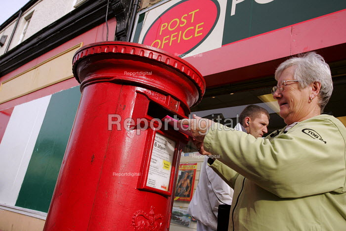 A woman posts a letter into a traditional red postbox outside a Post Office, North Shields. - Mark Pinder - 2004-11-01
