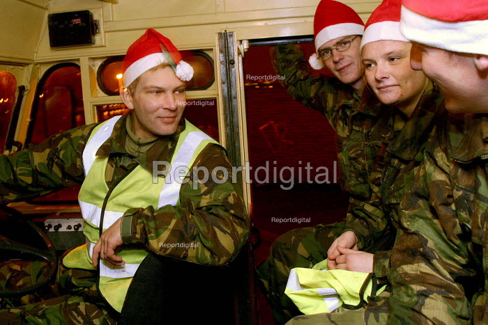 Soldiers manning a green goddess attending a minor fire at an industrial site in North Shields, Tyne and Wear. Wearing christmas santa hats in the green goddess given by a local resident who brought tea and biscuits. - Mark Pinder - 2002-11-24