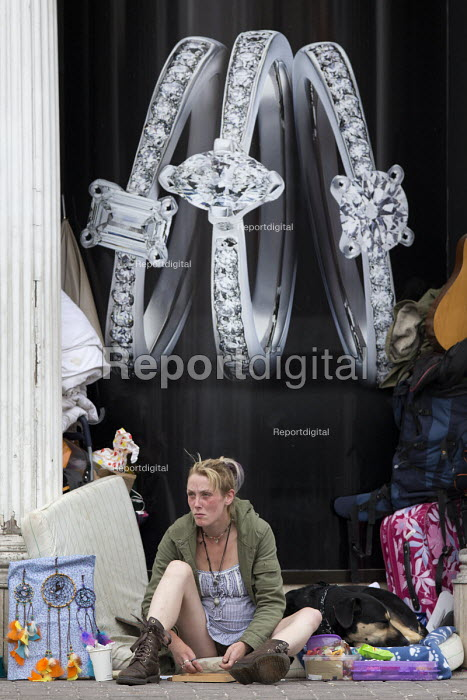 Homeless woman selling dreamcatchers below an advertisement for diamond rings in a closed shop doorway, Stratford-upon-Avon - John Harris - 2016-09-04