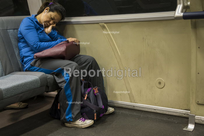 California, an exhausted passenger asleep on the Bay Area Rapid Transit train between San Francisco and Oakland - David Bacon - 2016-09-10
