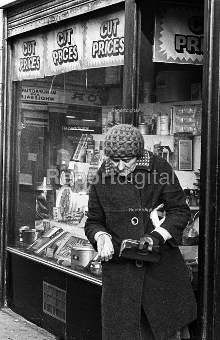 Pensioner checking her change outside a Cut Price shop in Tower Hamlets, one of the poorest boroughs in the UK, 1976. - Angela Phillips - 1976-02-12