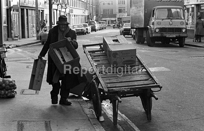 Man on street market collecting fruit and veg boxes, Tower Hamlets, one of the poorest boroughs in the UK, 1976. - Angela Phillips - 1976-02-12