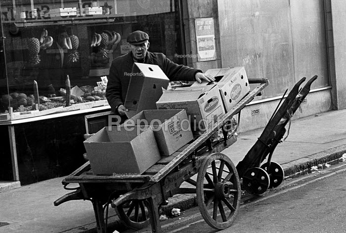 Market trader with empy fruit and veg boxes on his barrow,Tower Hamlets, one of the poorest boroughs in the UK, 1976. - Angela Phillips - 1976-02-12