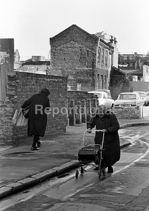 Pensioner pushing a pram along the street, Tower Hamlets, one of the poorest boroughs in the UK, 1976 - Angela Phillips - 1976-02-12