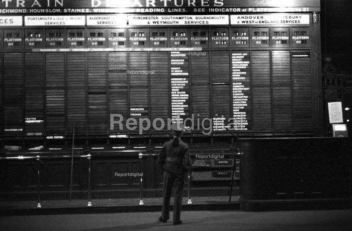 Soldier looking at the early morning train departures at Waterloo Station, London, 1959 - Alan Vines - 1959-10-23