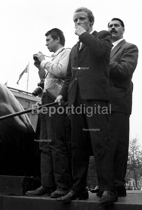 Photographer Don McCullin is working (L) by NSM members, one of whom is holding a long baton. National Socialist Movement fascist rally, Trafalgar Square 1962, leading to a riot after 'Free Britain From Jewish Control' speeches were heard by anti-fascist protestors opposing the fascist meeting. - Alan Vines - 1962-07-01