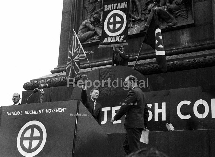 Fascist Colin Jordan approaches the podium and is given a Nazi salute less than two decades since the end of World War Two. National Socialist Movement fascist rally, Trafalgar Square 1962, leading to a riot after 'Free Britain From Jewish Control' speeches were heard by anti-fascist protestors opposing the fascist meeting. - Alan Vines - 1962-07-01
