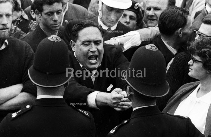 Police holding back anti-Fascist protestors trying to get to the NSM supporters. National Socialist Movement fascist rally, Trafalgar Square 1962, leading to a riot after 'Free Britain From Jewish Control' speeches were heard by anti-fascist protestors opposing the fascist meeting. - Alan Vines - 1962-07-01