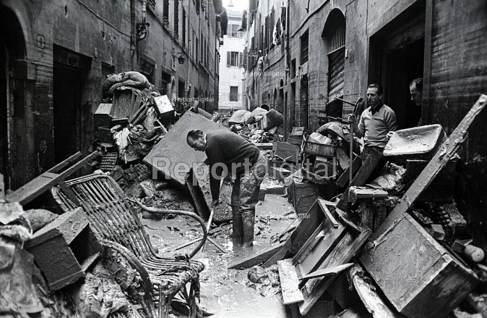 Clearing up, Florence Floods, Italy, 1966. The floods in Florence in early November 1966 were the worst in over five hundred years and resulted in the loss of over 100 Florentine lives as well as damage to thousands of cultural artefacts, including ancients books, paintings and sculptures. Florentines trying to restore some order to their flood damaged homes - Romano Cagnoni - 1966-11-14