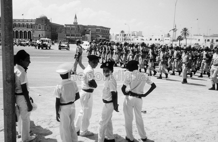 Young military cadets watching a Demonstration in support of Muammar Gaddafi, Tripoli 1984 on the 15th Anniversary of the coup that put him in control of Libya, later renaming it the Socialist Peoples Libyan Arab Jamahiriya. - Stefano Cagnoni - 1984-09-01