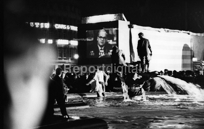 Labour Party victory in 1966 General Election. Crowds jumping into the fountains celebrating Labour General Election win in Trafalgar Square broadcast live on BBC TV with host Cliff Michelmore - Patrick Eagar - 1966-03-31