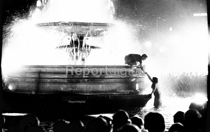 Labour Party victory in 1966 General Election. Crowds jumping into fountains celebrating Labour General Election win in Trafalgar Square broadcast live on BBC TV on a screen in the Square - Patrick Eagar - 1966-03-31