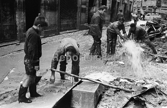 Clearing up, Florence Floods, Italy, 1966. The floods in Florence in early November 1966 were the worst in over five hundred years and resulted in the loss of over 100 Florentine lives as well as damage to thousands of cultural artefacts, including ancients books, paintings and sculptures. Florentines dealing with a water leak in the already flooded streets of the City - Romano Cagnoni - 1966-11-14