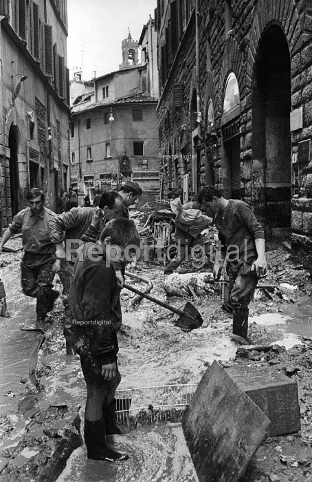 Clearing up, Florence Floods, Italy, 1966. The floods in Florence in early November 1966 were the worst in over five hundred years and resulted in the loss of over 100 Florentine lives as well as damage to thousands of cultural artefacts, including ancients books, paintings and sculptures. Florentines clearing their homes and the streets of the mud and debris caused by the flood. - Romano Cagnoni - 1966-11-14