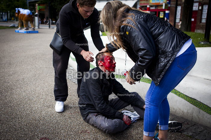 Man who has been assulted as he sat on a bench in theCity Centre being helped by the public. Sheffield centre, South Yorkshire - Connor Matheson - 2016-07-13