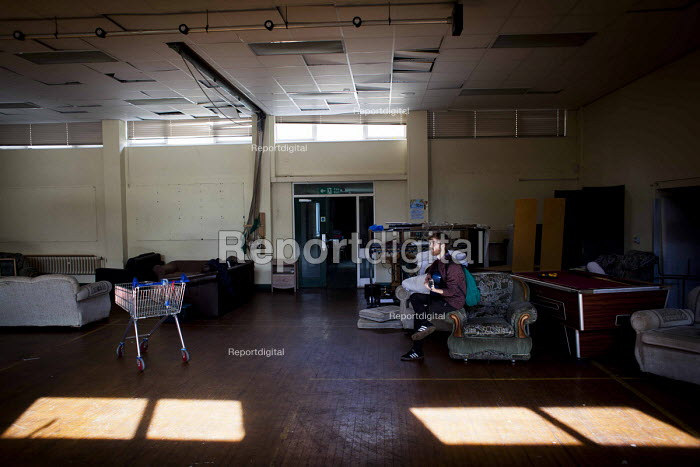 Young man playing guitar inside a disused school. Under a guardian scheme people are allowed to live there for a small rent as long as they take care of the building. St Margaret Of Antioch C Of E Primary School, Liverpool - connor matheson - 2016-09-25