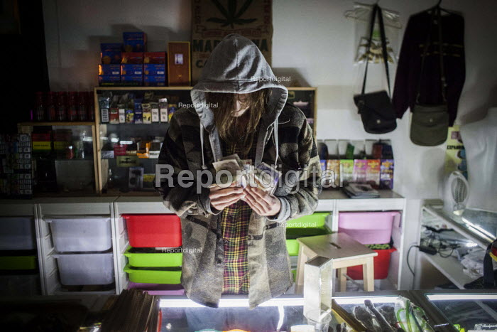 An event promoter counts his cash at the Golden Harvest headshop. Sheffield city center, South Yorkshire. - Connor Matheson - 2016-05-14