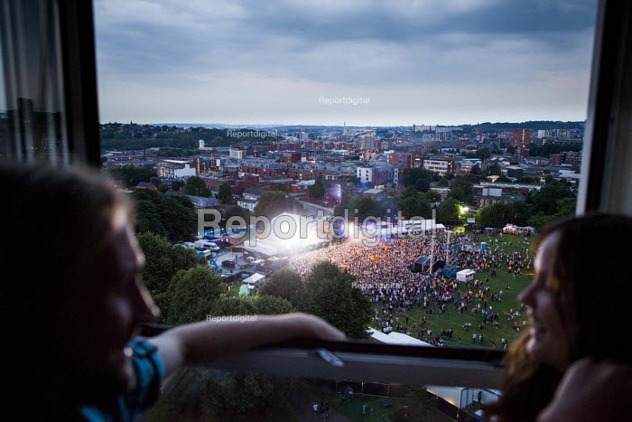 Council housing tenants and their friends watching a band performing at the Tramlines Music festival main stage from the window of a tower block flat. They do this to avoid paying for expensive tickets. Upperthorpe, Sheffield, South Yorkshire - Connor Matheson - 2016-07-22