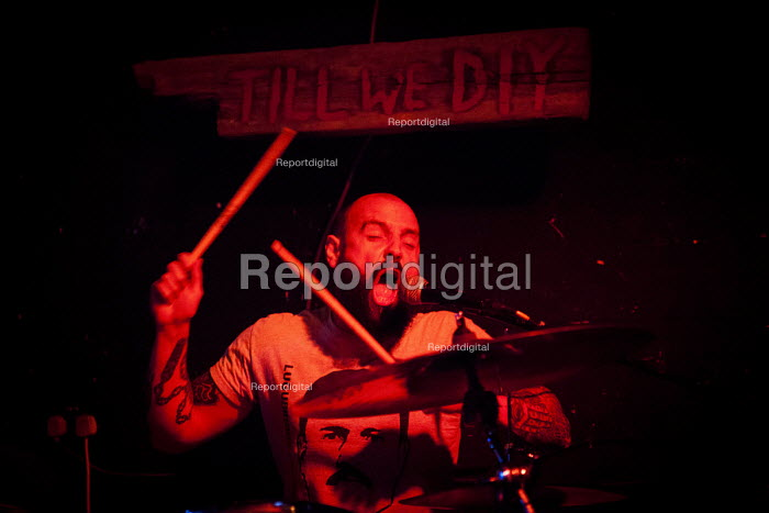 Punk drummer under a sign that says Till We D.I.Y at tempory venue, The Lughole. Sheffield city center, South Yorkshire - Connor Matheson - 2016-08-16