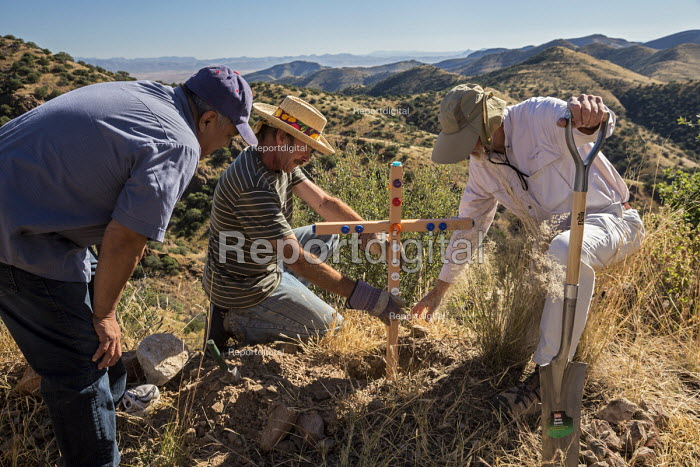 Bisbee, Arizona, USA, Christians put a cross in Mule Mountains near the spot where the remains of an unidentified migrant were found. Hundreds of migrants from Mexico and Central America have died crossing in recent years as they tried to evade U.S. Border Patrol checkpoints. More than 400 crosses in the Arizona desert have been planted by Members of the School Sisters of Notre Dame and other groups now mark the spots where they died. The cross is decorated with bottle caps found in the desert from water bottles carried by migrants. - Jim West - 2016-10-14