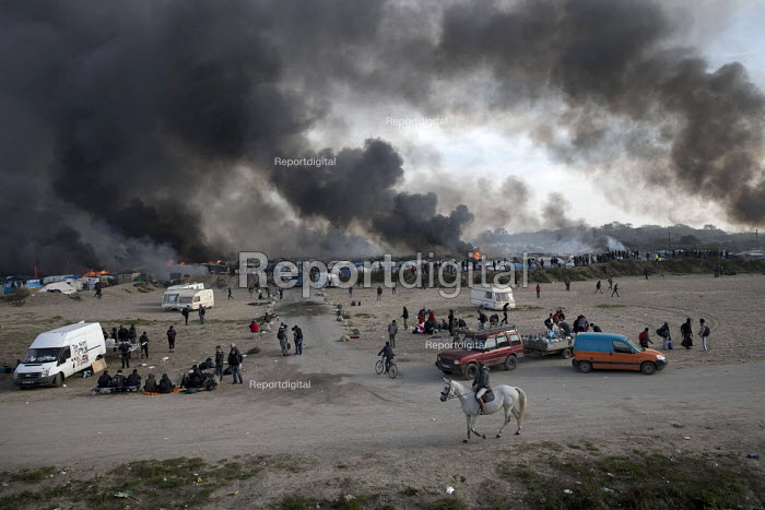 Local on horseback as fires rage during the eviction of refugees in the Jungle camp, Calais, France - Jess Hurd - 2016-10-26