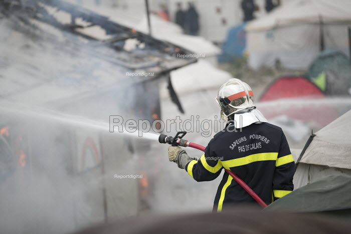Firefighter spraying fires during the eviction of refugees from the Jungle camp, Calais, France - Jess Hurd - 2016-10-26