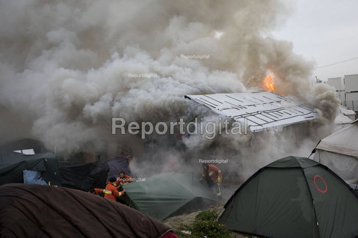 Volunteer firefighters try and save tents as fires rage during the eviction of refugees from the Jungle camp, Calais, France - Jess Hurd - 2016-10-26
