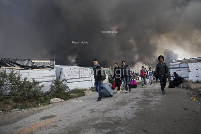 Refugees hastily leaving the camp as fires rage during the eviction of refugees from the Jungle, Calais, France. - Jess Hurd - 2016-10-26