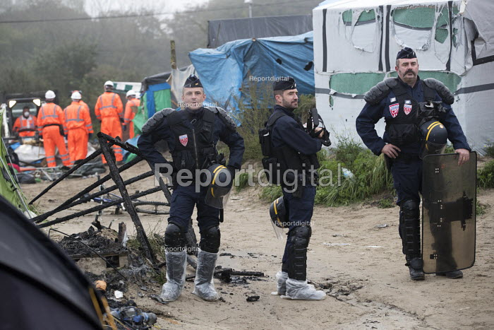 Police march into the Jungle camp to start the eviction. Calais, France. - Jess Hurd - 2016-10-26