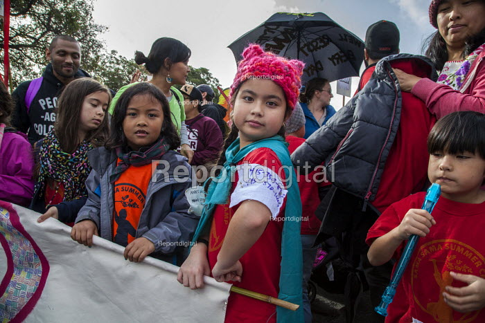 Oakland, California, USA, Womens March Against Trump. Filipino contingent organized by Filipino Advocates for Justice. Child wearing a label with her phone number in case they were separated from their parents in the huge crowd - David Bacon - 2017-01-21