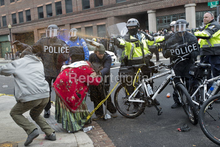 Washington DC, Police pepper spraying a Standing Rock protester during anti Trump protests on Inauguration Day as Donald Trump takes office as President of USA - Jess Hurd - 2017-01-20