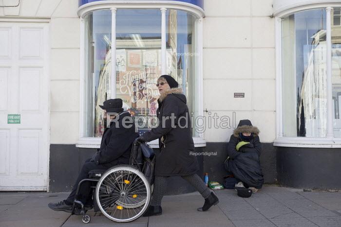 Disable man passing homeless beggar, Stratford-upon-Avon, Warwickshire. Happy Valentines Day window display - John Harris - 2017-02-04