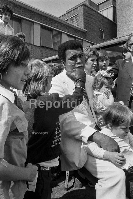 A boy lands a punch on Muhammad Ali during his visit to Great Ormond Street hospital, London 1977, he was visiting the famous paediatric hospital to help raise money for it - NLA - 1977-08-11