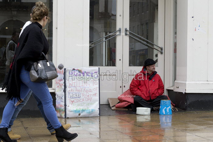 Homeless man begging in the doorway of closed shop, Leamington Spa, Warwickshire. Sign says he will do any work offered. - John Harris - 2017-03-22