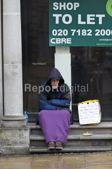 Homeless man begging in the doorway of closed shop, Leamington Spa, Warwickshire. Ex offender his sign says he will do any work offered. - John Harris - 2017-03-22