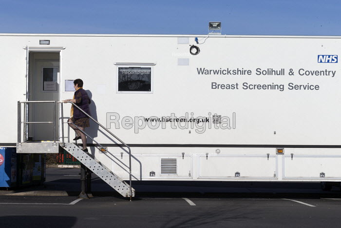 Woman attending Warwickshire Solihull & Coventry Breast Screening Service for a mammogram at a mobile clinic in a car park, Stratford-upon-Avon - John Harris - 2017-04-03