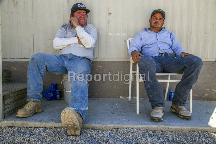 Coachella Valley, California, Two palmeros sitting in the shade of the trailer where they live on a trailer park near Thermal after work. Both have worked over 15 years in the in the date palm groves - David Bacon - 2017-04-03