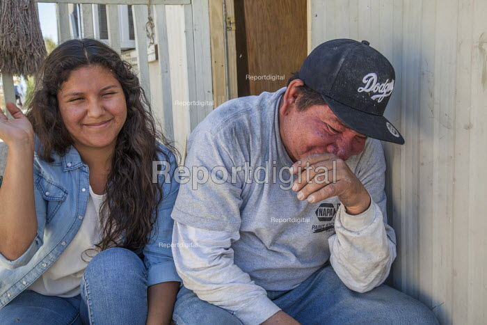Coachella Valley, California, a palmero sitting after work with his daughter in the shade of the trailer where they live on a trailer park near Thermal. She is trying to win a scholarship so she can go to college - David Bacon - 2017-04-03