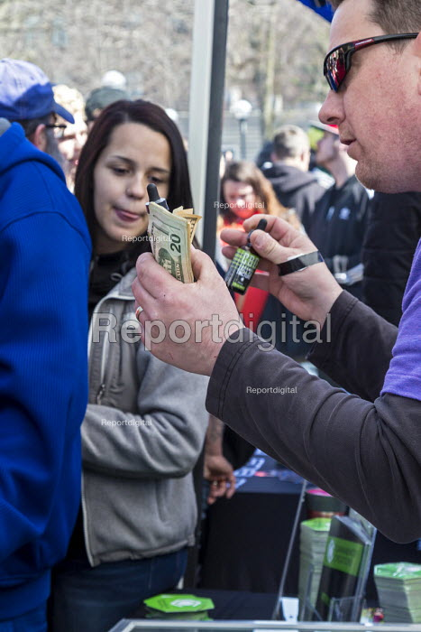 Ann Arbor, Michigan USA. A vendor sells non psychoactive tinctures made from industrial hemp. Thousands attended the annual Hash Bash a 45-year tradition advocating the legalization of marijuana, University of Michigan - Jim West - 2017-04-01
