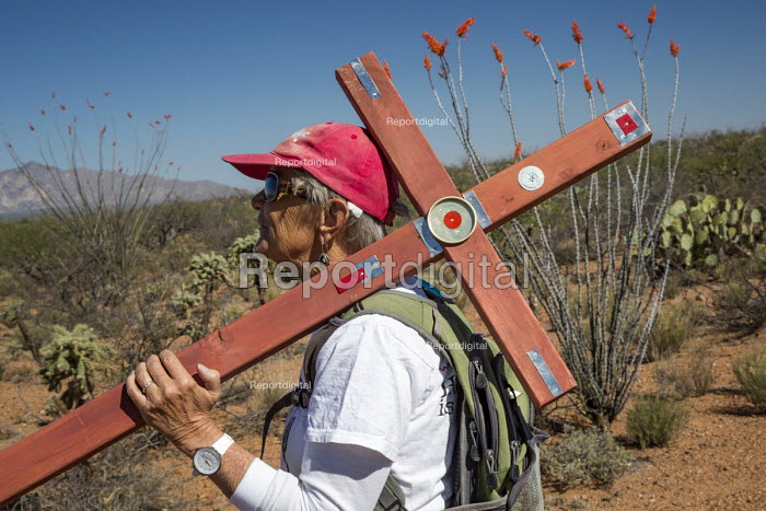 Tucson, Arizona, USA Mexican Border, Tucson Samaritans placing crosses in the desert where the remains of immigrants were found. Hundreds of migrants from Mexico and Central America die trying to evade US Border Patrol checkpoints. More than 500 crosses planted in Arizona by the Samaritans and other groups now mark where they died. Mary Toethals carries a cross to mark the spot where an unidentified migrant died. - Jim West - 2017-04-18