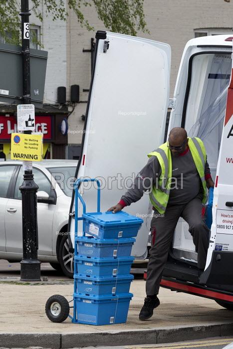 Van driver making a delivery, unloading onto a trolly, Stratford upon Avon, Warwickshire - John Harris - 2017-04-26