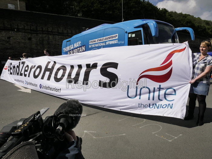 Unite the Union unfurl a banner in front of Conservative Party battle bus against zero hours contracts. Conservatives manifesto launch, Dean Clough Mills, Halifax, Yorkshire, 2017 General Election campaign - Mark Pinder - 2017-05-18
