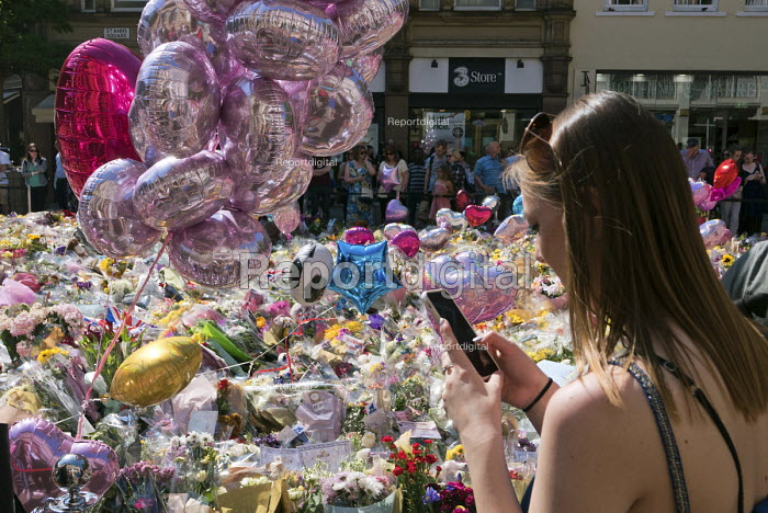 Woman takes a mobile phone photo of the flowers, candles, balloons and other tributes to the victims of the Manchester Arena terrorist bomb, St Anns Square, Manchester, UK - Paul Herrmann - 2017-05-26