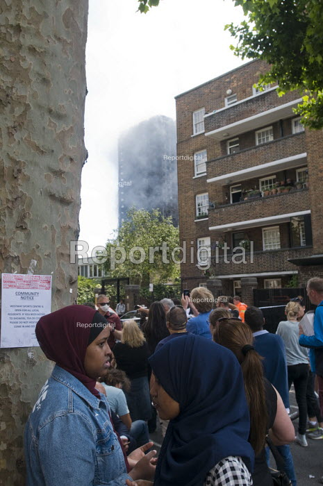 Grenfell Tower Fire. Local residents look on as smoke can be seen still smouldering a full 12 hours after the raging inferno that engulfed the West London tower block seen in the near distance resulting in the loss of many lives - Stefano Cagnoni - 2017-06-14