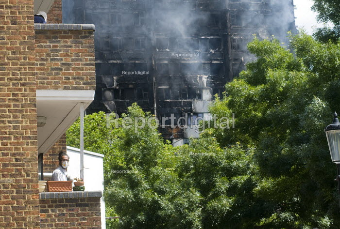 Grenfell Tower Fire. Local resident on his balcony wears a mask to filter fumes from the smoke still smouldering a full 12 hours after the raging inferno that engulfed the West London tower block seen in the background - Stefano Cagnoni - 2017-06-14