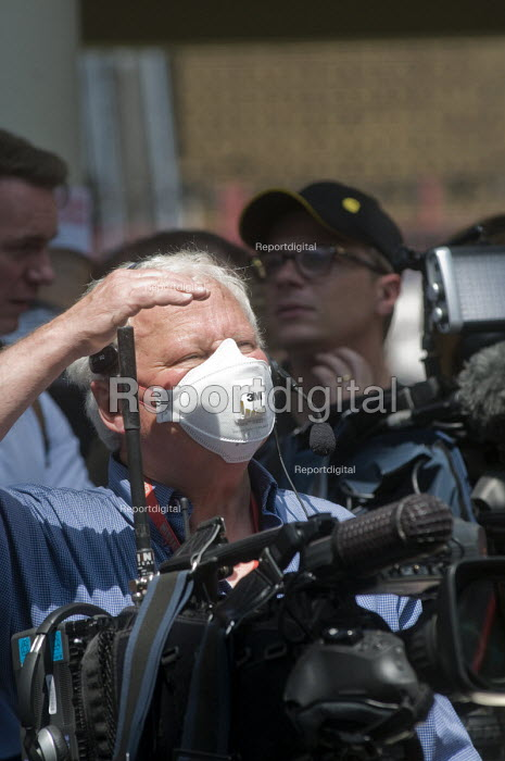 Grenfell Tower Fire. TV News camera operator wearing a mask to protect himself from the fumes and smoke a full 12 hours after the raging inferno that engulfed the West London tower block resulting in the loss of many lives - Stefano Cagnoni - 2017-06-14