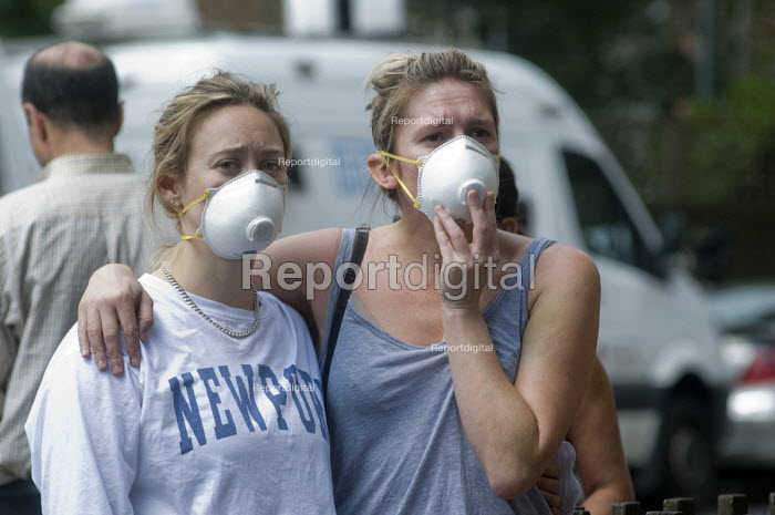 Grenfell Tower Fire. Residents from the local community comfort each other whilst wearing masks to protect them from the smoke and fumes still in the air more than 12 hours after in the fire that engulfed the West London tower block overnight - Stefano Cagnoni - 2017-06-14