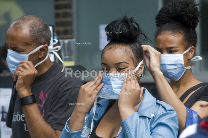 Grenfell Tower Fire. Local residents outside the Latymer Community Centre in West London just a few hundred metres from Grenfell Tower help each other don masks to protect them from the smoke and fumes still in the air more than twelve hours after the fire that engulfred the tower block overnight - Stefano Cagnoni - 2017-06-14