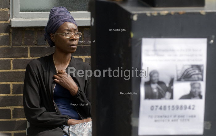 Grenfell Tower Fire. Worried local resident outside the Latymer Community Centre in West London with a Missing Persons sign to her right just a few hundred metres from the tower block engulfed by fire overnight - Stefano Cagnoni - 2017-06-14